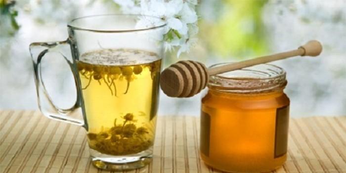 Чашка с отваром ромашки и банка меда