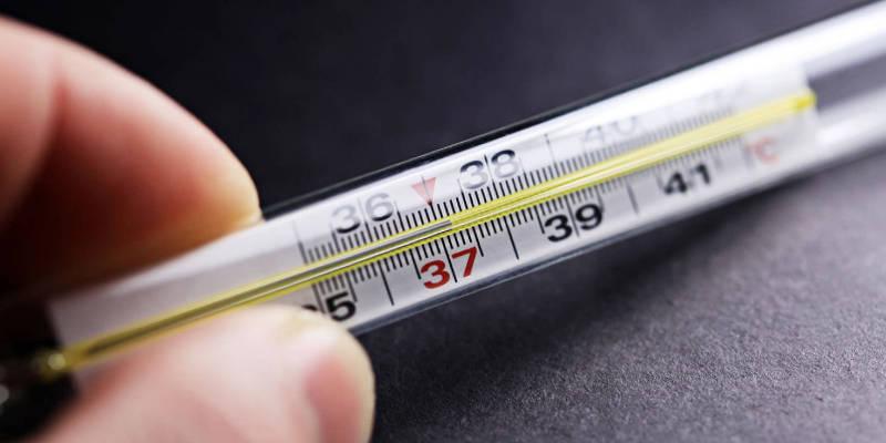Рука держит градусник с показаниями 37,2