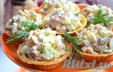 Заполнить тарталетки аппетитным, ярким салатом с ветчиной и огурцами, украсить зеленью. Вкусная закуска готова.