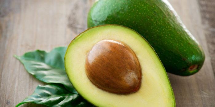 Авокадо разрезанное пополам и целое