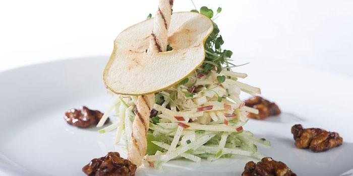 Уолдорфский салат на тарелке с чипсой из груши и орехами