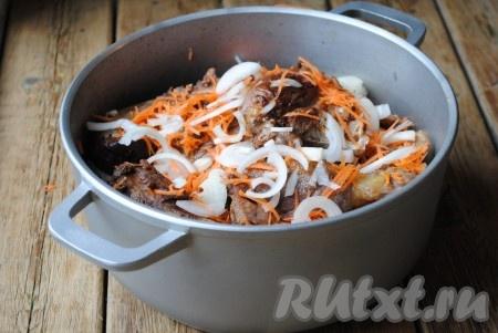 Лук и морковь очистить. Лук нарезать полукольцами, морковь натереть на средней тёрке. Обжаренные кусочки утки выложить в казан или толстостенную кастрюлю, чередуя с луком и морковкой.